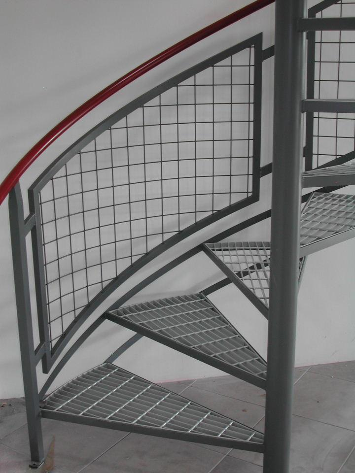 Custom Interior Spiral Stair With Wire Mesh Infill And Bar Grate Treads.  Handrail Is Painted A Different Color Then The Rest The Stair And Railing.